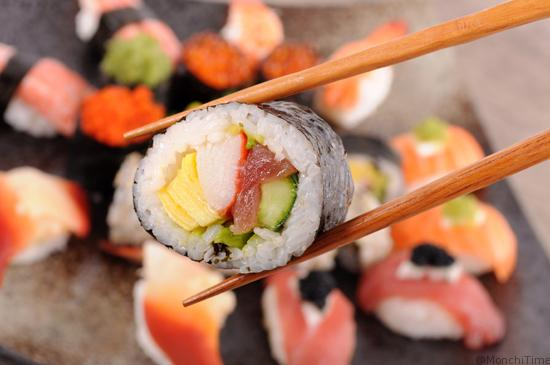 Futomaki sushi held by chopsticks against a background of assorted sushi platter.(photo credit:  iStock)